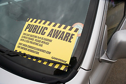 Greenpeace sticker on car windscreen warning about climate change caused by unclean car emissions pollution,