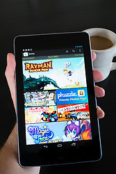 Man holding  Google Nexus tablet computer running android showing games for sale at Google Play store