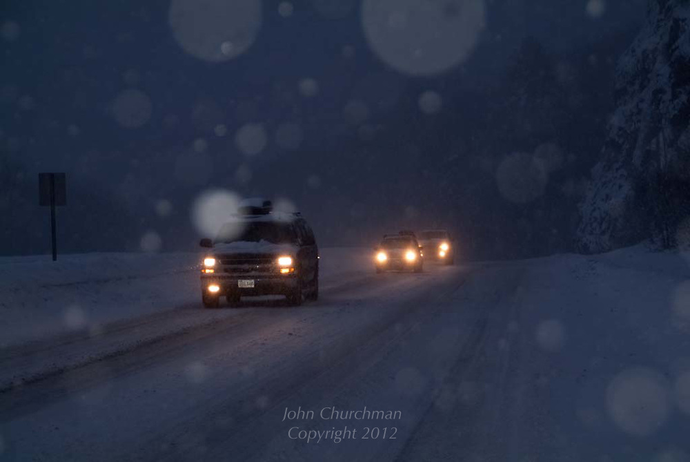 winter snow scene, head lights on, highway driving conditions, dark, stormy