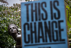"© Licensed to London News Pictures. 30/08/2020. Manchester, UK. A protester raises a placard reading "" This is Change "" in front of a statue dedicated to Robert Peel , in Piccadilly Gardens . The statue features two subsidiary allegorical female figures , one of which is pictured . Protesters and campaigners hold a combined Extinction Rebellion and Black Lives Matter protest in Manchester City Centre , during which statues and memorials are rededicated with new historical context highlighting the slave trade . Photo credit: Joel Goodman/LNP"