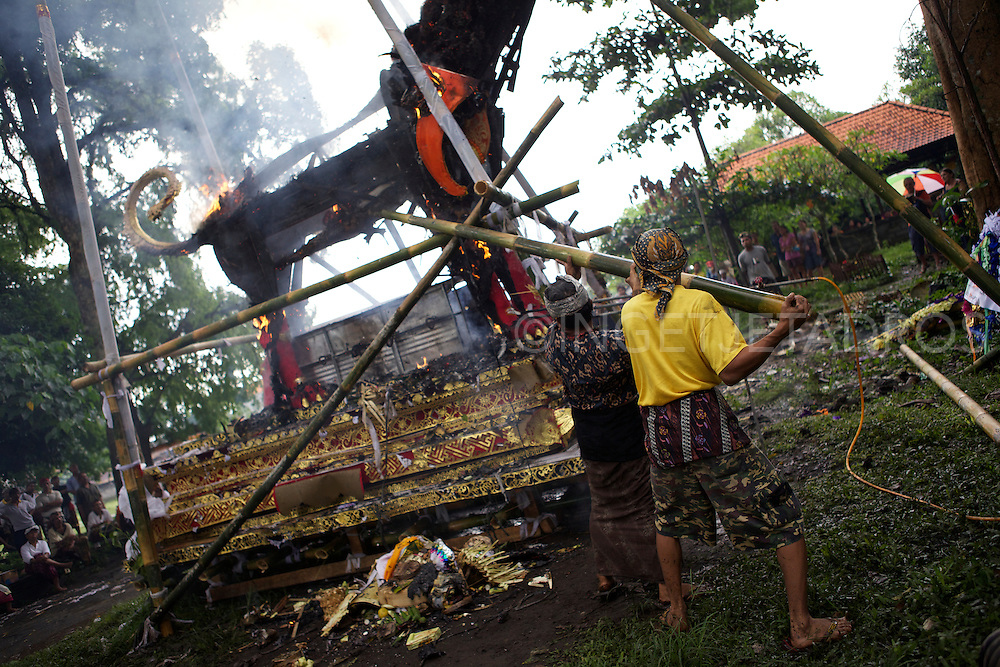 Family and friends are sitting in a circle around the burning dragon, while men attending the fire.<br />
