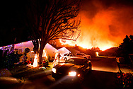 People evacuate their home as a wildfire burns on a mountain behind homes in Santa Paula, California, the United States in the early morning hours of Tuesday Dec. 5, 2017. Authorities say the fire has claimed one life, charred 10,000 acres and has destroyed multiple structures.