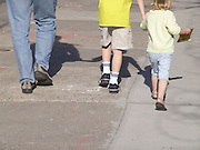 Parent walking with two children.