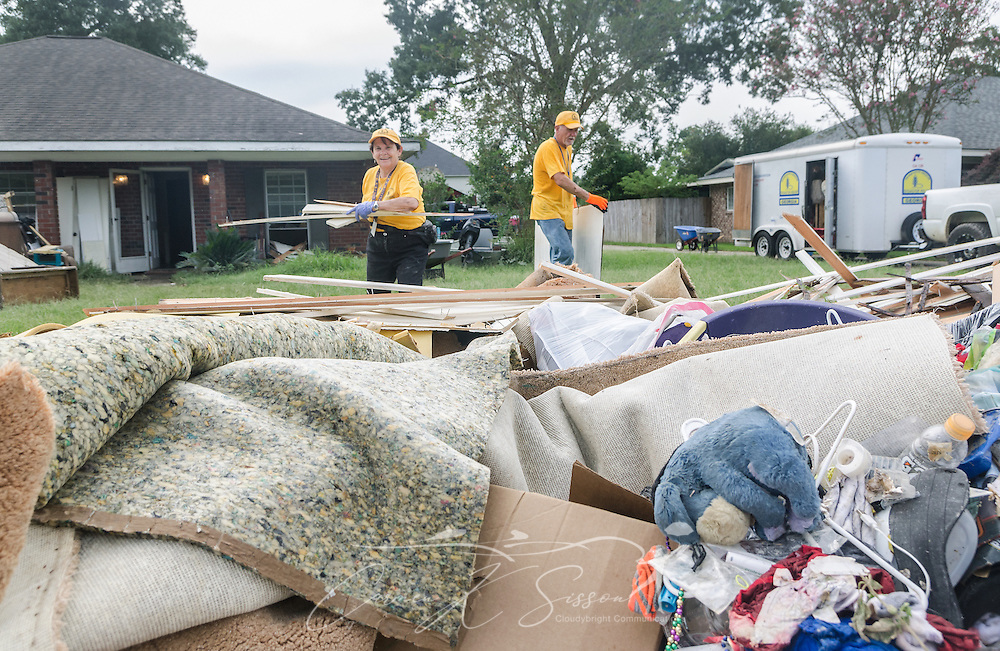 Southern Baptist Disaster Relief chaplain Joan Sangster, a member of Calvary Baptist Church in Jesup, Ga., and Jim Rabon, of Compassion Christian Church in Savannah, Ga., carry flood-damaged wood to a garbage heap, Aug. 26, 2016, in Denham Springs, La. Sangster and Rabon, along with other SBDR Georgia volunteers, are at the home of Karen Johnson and Phillip Carpenter this week, helping them mud out their flood-damaged home. Johnson and Carpenter, members of Immaculate Conception Church in Baton Rouge, are among thousands of Louisiana residents affected by a mid-August flood. (Photo by Carmen K. Sisson)