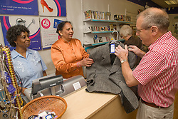 Women volunteers serving a customer in a charity shop,
