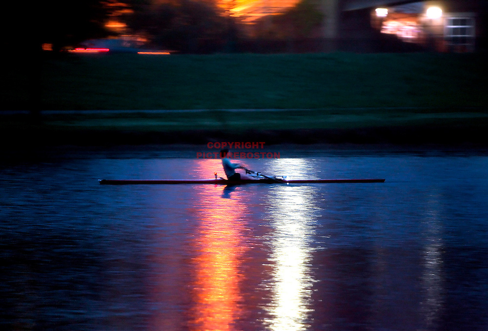 A rower along the Charles River at night.