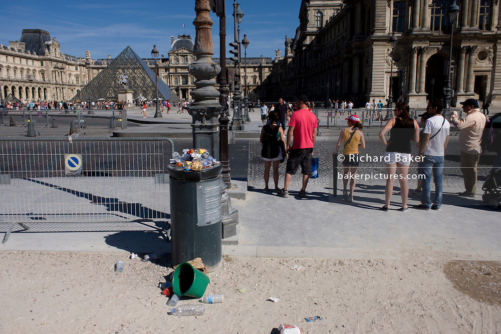 Overflowing litter bins and tourists at the entrance of the Tuillerie Gardens outside the Louvre art museum.