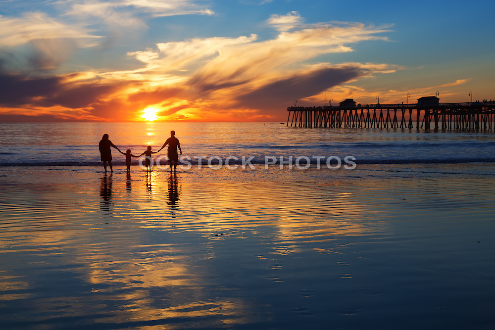Family of Four Holding Hands on the Beach During Sunset in San Clemente