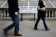 Blurred pedestrians pass the street sign on a Westminster pavement, where Parliament Street becomes Whitehall, the centre for government buildings.