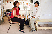 16 JULY 2007 -- NOGALES, SONORA, MEXICO: FREDERICO LAVIDA, an immigrant from the Mexican state of Oaxaca, talks to SILVIA GONZALEZ, a social worker from the Mexican state of Sonora, at the No More Deaths aid station near the Mexican port of entry in Nogales, Sonora, Mexico. No More Deaths and the Sonora state government set up the aid station in 2006 to help Mexican immigrants deported from the US from across the US Border Patrol station in Nogales, Arizona. Volunteers at the aid station provide immigrants, many of whom spend days in the desert before being apprehended by the US Border Patrol, with food and water and rudimentary first aid. The immigrants then go back to their homes in Mexico or into Nogales to make another effort at crossing the border. Volunteers said they help between 600 and 1,000 immigrants per day. The program costs about .60¢ per person to operate. So far this year they've helped more than 130,000 people.  Photo by Jack Kurtz/ZUMA Press