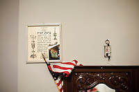 """27 October, 2008. New York. An American flag and a portrait of Rabbi Menachem Mendel Schneerson are here in Faina Ryzhikova's apartment. Faina El'man Ryzhikova, 82, a Jewish holocaust survivor and guerilla fighter, lives in Bensonhurst, Brooklyn, NY. After asking for help, the Edith and Carl Marks Jewish Community House of Bensonhurst assisted her by tapping The New York Times Needieset funds for utility expenses of $50/month for 6 months, the first grant starting on October 3, 2008.<br /> <br /> Faina Ryzhikova was born in 1926 in Radoshkovichi, a little village 22 miles northwest from Minsk, Belarus. Back in 1939, this territory belonged to Poland. When the Germans occupied Radoshkovichi, in 1941, they created a ghetto, where Faina and her family lived and worked. In order to escape a planned pogrom by the Germans in 1942, Faina escaped into the forest where she later met the partisans of the brigade """"Narodnie Mstiteli"""" (Avengers of the people), which she joined.<br /> <br /> Faina's mother and sisters were killed while trying to escape. Her father survived and joined aina in 1943. Of the 2000 people that lived in the Radoshkovichi ghetto, only 18 survived. She married Vladimir Ryzhikov in 1954 and raised two sons. Faina's husband passed away in 1991, before the family came to the United States.<br /> <br /> <br /> ©2008 Gianni Cipriano for The New York Times<br /> cell. +1 646 465 2168 (USA)<br /> cell. +1 328 567 7923 (Italy)<br /> gianni@giannicipriano.com<br /> www.giannicipriano.com"""