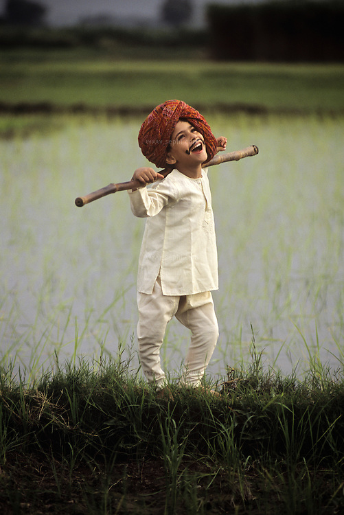 A young boy dressed as a farmer in a farm ourside of delhi, India.