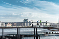 Runners from the Copenhagen Running Club NBRO Runners race across a structure high above the harbour waters, known as Bølgen (the wave)