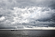 A Lake Erie fishing boat returns to the Port Stanley harbour under stormy skies.