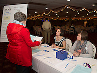 Shanna B. Saunders and Brandee Loughlin welcome guests to the Re Imagine Laconia event at the Opechee Conference Center on Wednesday evening.  (Karen Bobotas Photographer)