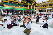 15 JUNE 2013 - YANGON, MYANMAR: People pray on a plaza on the northeast side of Shwedagon Pagoda. The Shwedagon Pagoda is officially known as Shwedagon Zedi Daw and is also called the Great Dagon Pagoda or the Golden Pagoda. It is a 99 metres (325ft) tall pagoda and stupa located in Yangon, Burma. The pagoda lies to the west of on Singuttara Hill, and dominates the skyline of the city. It is the most sacred Buddhist pagoda in Myanmar and contains relics of the past four Buddhas enshrined: the staff of Kakusandha, the water filter of Koṇāgamana, a piece of the robe of Kassapa and eight strands of hair fromGautama, the historical Buddha. The pagoda was built between the 6th and 10th centuries by the Mon people, who used to dominate the area around what is now Yangon (Rangoon). The pagoda has been renovated numerous times through the centuries. Millions of Burmese and tens of thousands of tourists visit the pagoda every year, which is the most visited site in Yangon.   PHOTO BY JACK KURTZ