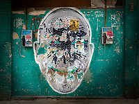 A giant stencilled head flanked by two payphones in Havana Centro.