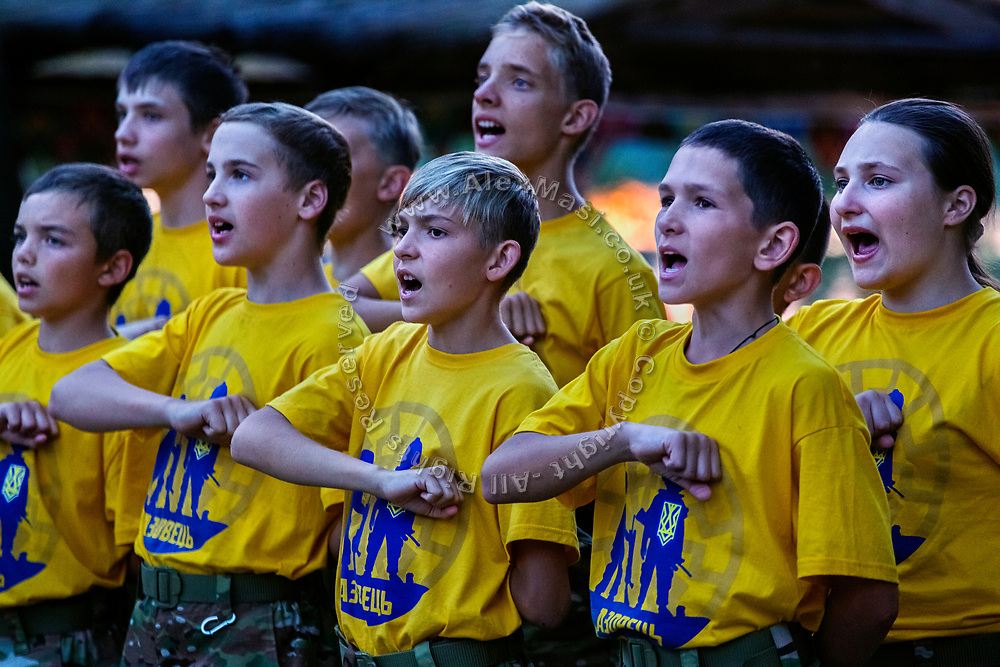 Youngsters participating to the ultra-nationalistic Azovets children's camp are attending a regular ceremony and chanting patriotic slogans with their fists up against their hearts, on the banks of the Dnieper river in Kiev, Ukraine's capital.