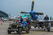 North American P-51D Mustang (Miss Hellen) is towed out to the stand by a WWII Jeep - Duxford Battle of Britain Air Show taking place during IWM (Imperial War Museum) Duxford's centenary year. Duxford's principle role as a Second World War fighter station is celebrated at the Battle of Britain Air Show by more than 40 historic aircraft taking to the skies.