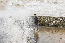 © Licensed to London News Pictures. 31/12/2017. Brighton, UK. A man just escapes being soaked by a large wave that hits the Brighton and Hove seafront on 2017 New years eve. Photo credit: Hugo Michiels/LNP