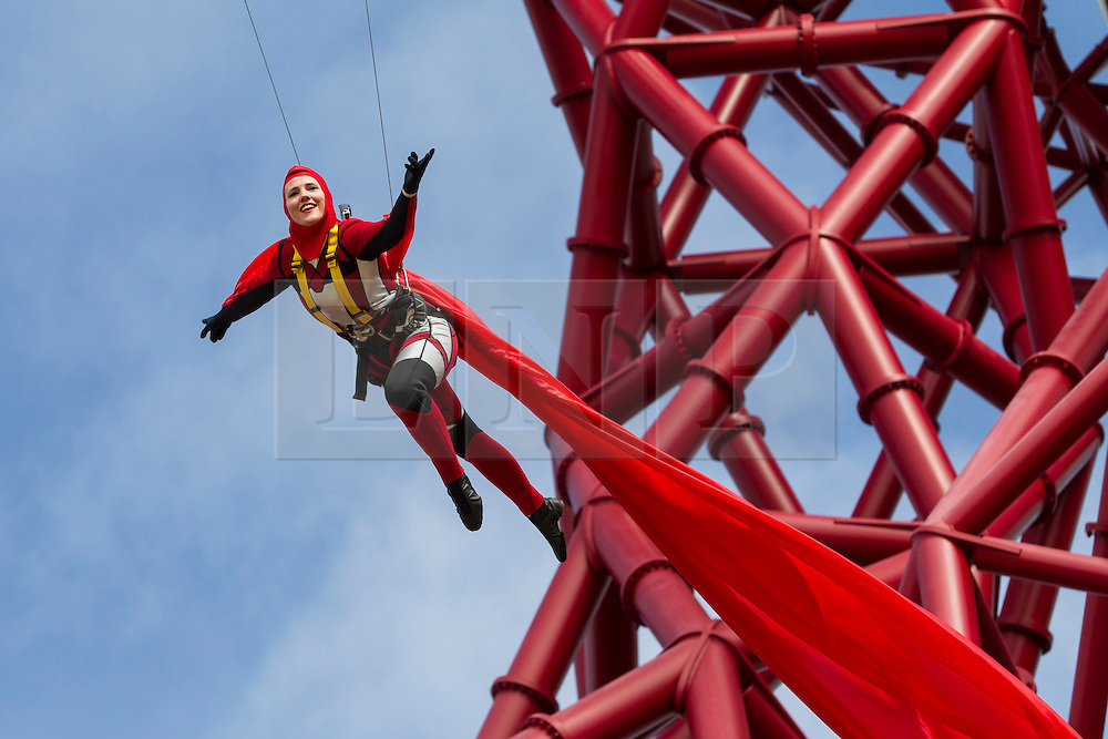 © Licensed to London News Pictures. 05/04/2014. Acrobats perform 80 metres above East London to celebrate the official public opening of the ArcelorMittal Orbit in Queen Elizabeth Park, Stratford. Photo credit : David Fearn/LNP