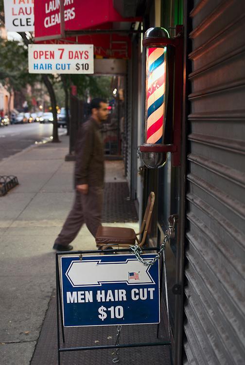 Barber pole and sign outside barber shop