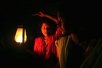 A woman holds a lamp for a female Maoist rebel of the PLN, People?s Liberation Army, in a rebel-controlled region of western Nepal on June 20, 2006. In November or 2006, after 10 years of fighting and over 13,000 deaths, the rebels and the government signed a peace deal that ended the war and allows the rebels to participate in government. But the peace is very fragile and the future of Nepal is uncertain. (Photo/Scott Dalton)