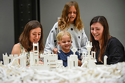 "© Licensed to London News Pictures. 26/07/2019. LONDON, UK. (C) Margot Cartwright-Naylor, aged 4, and her sister Stella, aged 11, work with Lego at the preview of ""The cubic structural evolution project"", 2004, by Olafur Eliasson at Tate Modern.  Exhibited for the first time in the UK, the artwork comprises one tonne of white Lego bricks inspiring visitors to create their own architectural vision for a future city and is on display until 18 August 2019.  The work coincides with the artist's new retrospective exhibition ""In real life"" at Tate Modern on display to 5 January 2020.  Photo credit: Stephen Chung/LNP"