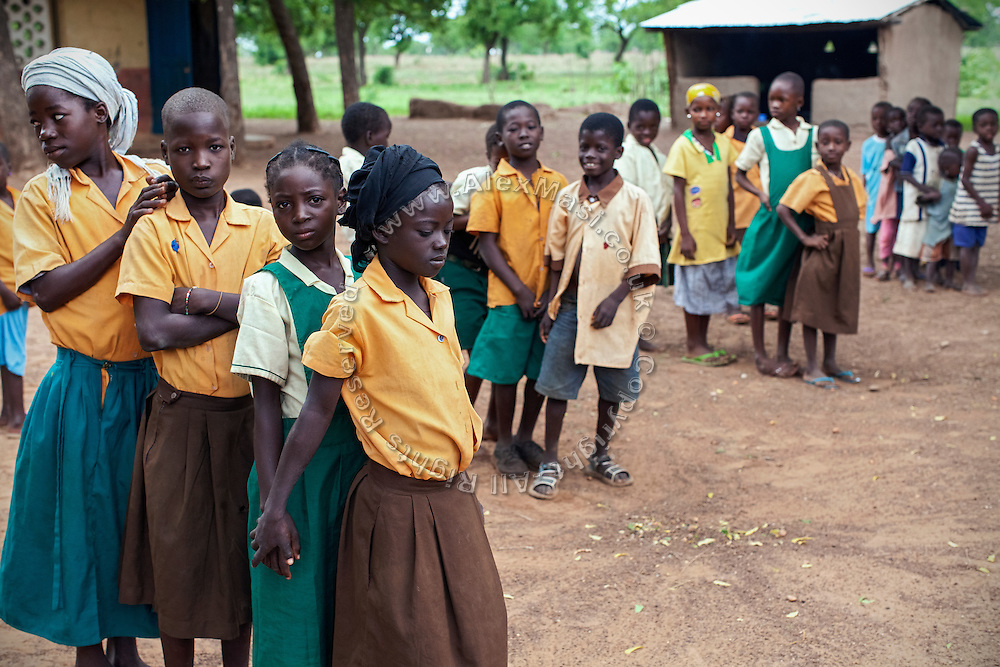 Hassana Ibrahim, 11, (front/second) and her classmate Rahima Ibrahim, 11, (front/first, not sisters) are waiting to enter their classes, after having formed a straight line with other students in the courtyard of their school in Boggu, Tamale, northern Ghana.