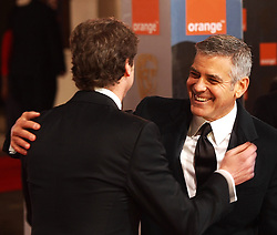 U.S. actor George Clooney, right, hugs British actor Colin Firtharrives for the 2012 ORANGE BRITISH ACADEMY FILM AWARDS, The Bafta's at The Royal Opera House, Covent Garden, London. Photo By I-Images