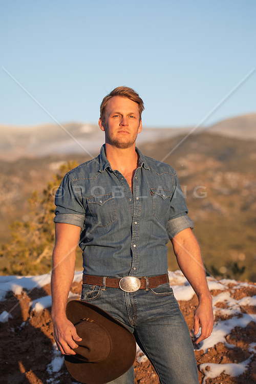 blond cowboy holding his cowboy hat outdoors on a mountain