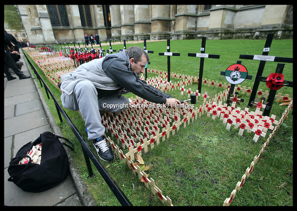 A volunteer places the  wooden crosses into the Field of Remembrance at Westminster Abbey in London, Tuesday 6th November 2012. The officially opening will be performed  by the Duke of Edinburgh  on Thursday  8th November 2012. Photo by: Stephen Lock / i-Images
