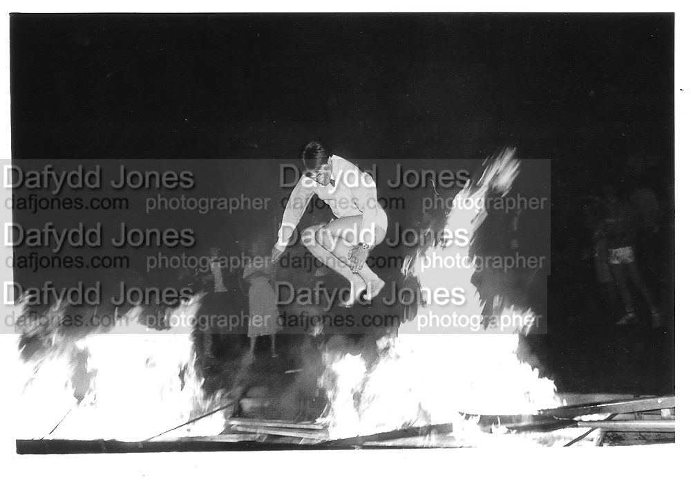 Paul Guerra jumping over a burning boat. Cambridge. 1983 approx. © Copyright Photograph by Dafydd Jones 66 Stockwell Park Rd. London SW9 0DA Tel 020 7733 0108 www.dafjones.com