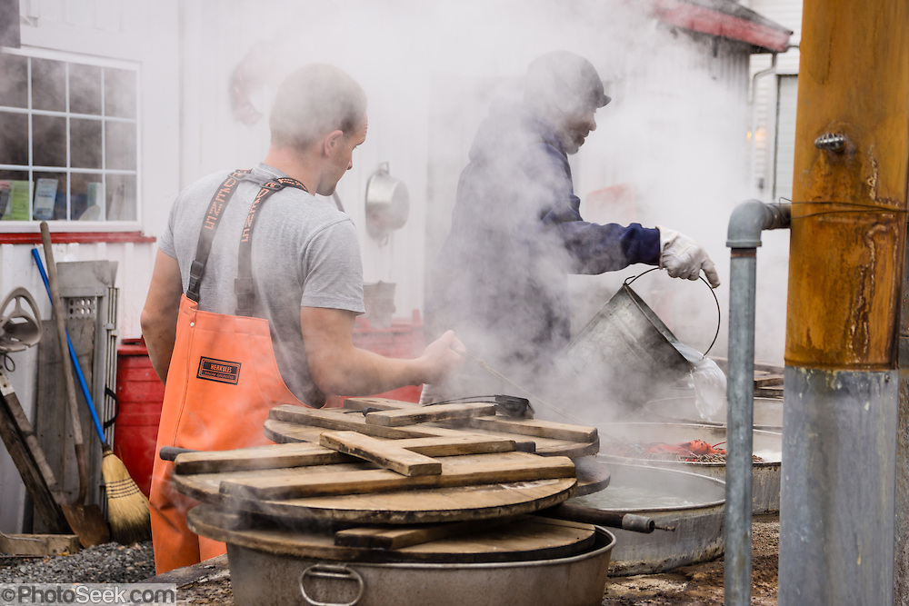 Workers tend steaming pots of boiling lobsters. Trenton Bridge Lobster Pound serves delicious lobsters boiled in fresh, clean seawater over a wood fire, plus other seafood. Address: 1237 Bar Harbor Rd, Trenton, ME 04605. Phone (207) 667-2977.