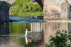 © Licensed to London News Pictures. 26/05/2020. Builth Wells, Powys, Wales, UK. A man fishes in the river Wye on a beautiful warm evening at Builth Wells in Powys, UK. Wales remains under lockdown. It has been remarked by some Welsh people that Mark Drakeford, First Minister of Wales, who has not followed Boris Johnson's actions, always seems to take the opposite stance of Westminster. Photo credit: Graham M. Lawrence/LNP