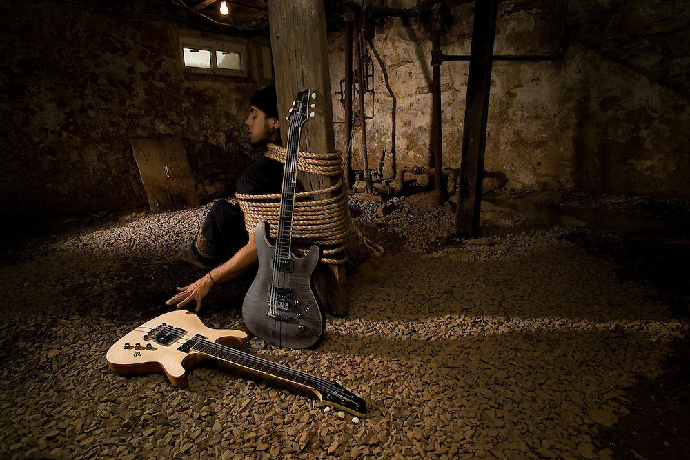 Scenes from imaginary films. Photograph for advertising campaign. Obsessed with playing his guitars, a young man has been tied to a post in the basement by his mother with his guitars just out of reach.