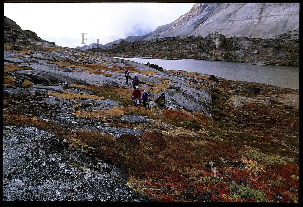 Clipper Adventurer cruise ship passengers hike by glacial tarn through colorful autumn tundra in late Aug; Tasiusaq Bay, Greenland