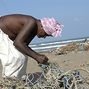 Chellakannu Thiruvenkatam, a fisherman, tries to untangle a net washed up on the shore of Perumalpettai, a fishing village in Tamil Nadu, India, after the area was struck by the Indian Ocean Tsunami on December 26, 2004, killing 37 of the villagers and destroying nearly all of their fishing boats. Generated by an earthquake on the ocean floor, the tsunami devastated the fishing industry along the southeastern coast of India.