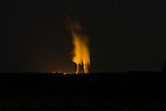 As the September night air cools, the towers at the Byron Nuclear Power Plant emit columns of steam into the dark sky.