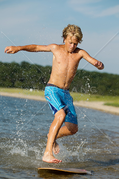 young boy playing on a skimboard in the Northwest Harbor in East Hampton, NY