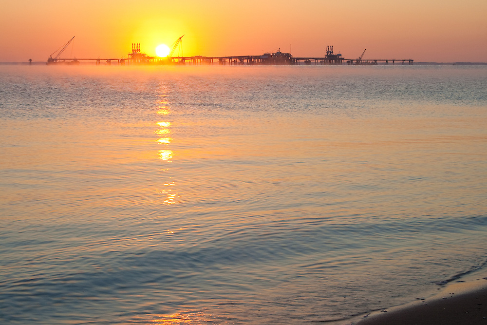 Sun rising over a cannery just offshore from the beach at Calvert Cliffs State Park, Lusby, Maryland