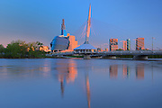 Canadian Museum for Human Rights (CMHR) and the Esplanade Riel Bridge and the Red River at sunrise<br /> Winnipeg<br /> Manitoba<br /> Canada<br /> Winnipeg<br /> Manitoba<br /> Canada