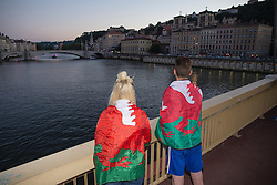 LYON, FRANCE - Tuesday, July 5, 2016: Two Wales supporters wrapped in flags look out over the river Saone towards Lyon ahead of the UEFA Euro 2016 Championship Semi-Final match against Portugal at the Stade de Lyon. (Pic by Paul Greenwood/Propaganda)