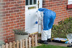 © Licensed to London News Pictures. 09/01/2020. Didcot, UK. A Thames Valley Police forensic investigator gathers evidence after blood was discovered on a house door, the crime scene in the Mendip Heights estate is close to where three men were injured during an incident and were taken to hospital for treatment. One of the men, aged in his forties was later pronounced dead and a murder investigation was launched. The victim received multiple stab wounds. Two other victims, one man in his twenties and another man in his thirties, are in serious but stable conditions in hospital. Photo credit: Peter Manning/LNP