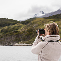 A woman photographs from a sightseeing boat on the Beagle Channel in Parque Nacional Tierra del Fuego, near Ushuaia, Argentina.