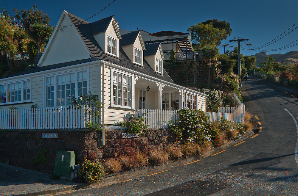 Morning sunlight on a traditional New Zealand cottage with dormer windows and white picket fence, Bridle Path, Lyttelton