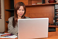 Young woman very happy working in a laptop in small office.