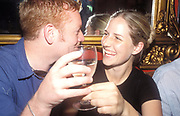 Man and woman looking in the eyes, laughing and drinking white wine. 2004<br />