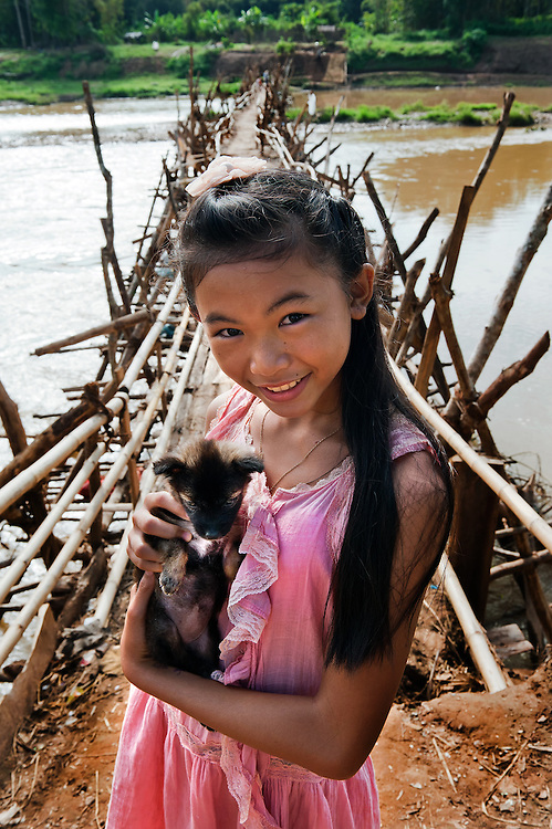 A girl with her puppy will cross the Nam Khan (river) over a bamboo bridge near luang Prabang, Laos.