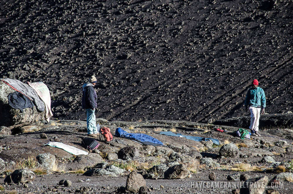 Two porters lay out their clothes and sleeping bags at Moir Hut Camp to try to dry them in the sunlight before they have to head off for that day's climb on Mt Kilimanjaro's Lemosho Route.
